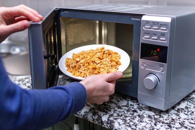 Usando un microondas para calentar un plato de pilaf casero para el almuerzo en casa. comida caliente