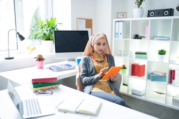 Usando tableta. profesora joven ocupada con hijab usando su tableta mientras lee un libro electrónico