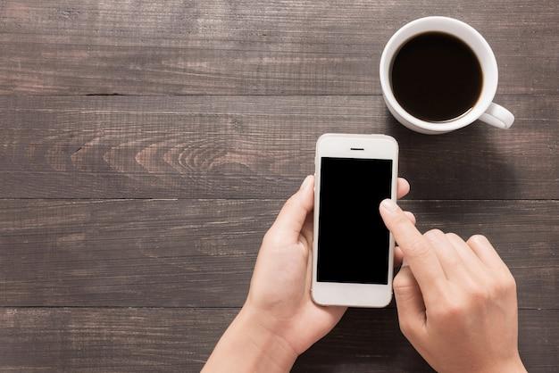 Usando el teléfono inteligente al lado de café en la mesa de madera