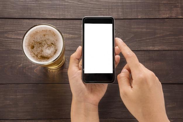 Usando el teléfono inteligente al lado de cerveza en el pub