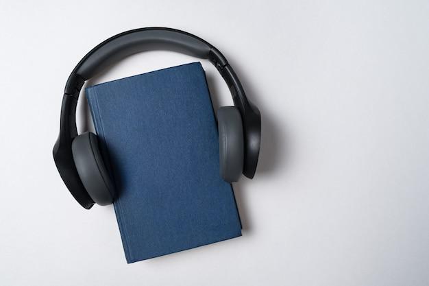 Usando tus auriculares en el libro. concepto de audiolibros. fondo blanco copia espacio.