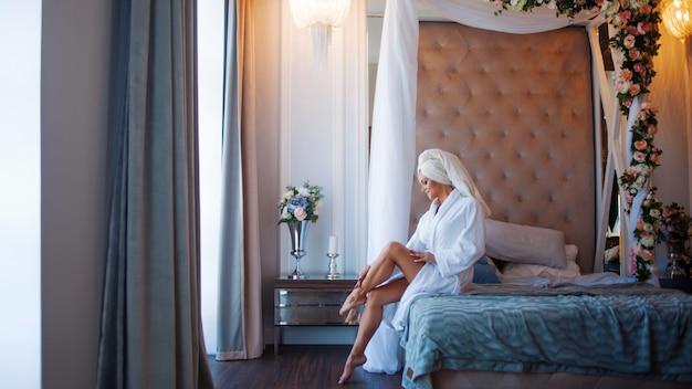 Usar la crema para el cuerpo. mujer joven en una bata de baño, interior del hotel