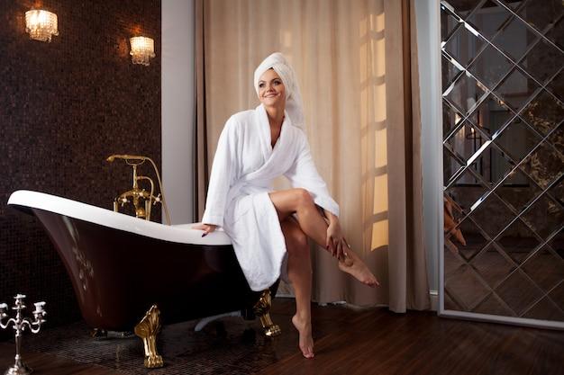 Usar la crema para el cuerpo. mujer joven en el salón de spa, el interior del hotel.