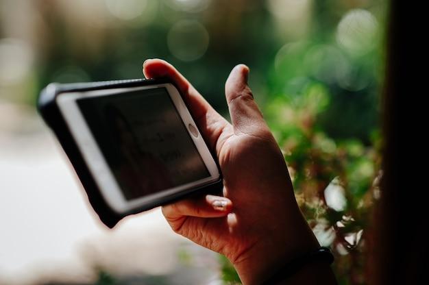 Usar los medios del teléfono para mirar películas durante el tiempo libre en la cafetería decorada en la naturaleza