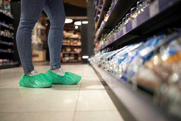 Usar zapatos de protección contra el virus corona en el supermercado