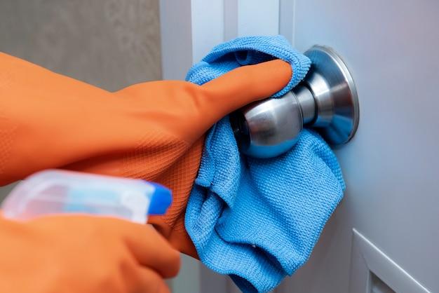 Use alcohol a mano para limpiar una perilla de acero inoxidable y una puerta de madera.