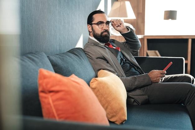 Use disfraz. empresario barbudo de pelo oscuro vistiendo traje sentado en el sofá descansar