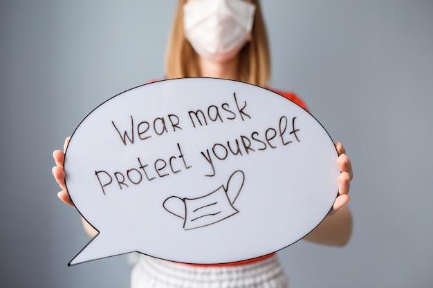 Use máscara: protéjase con la inscripción en el bocadillo en las manos de la mujer. la mujer lleva una máscara durante la epidemia covid 19.