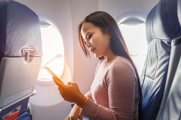 Uso asiático de la mujer del teléfono móvil dentro del aeroplano