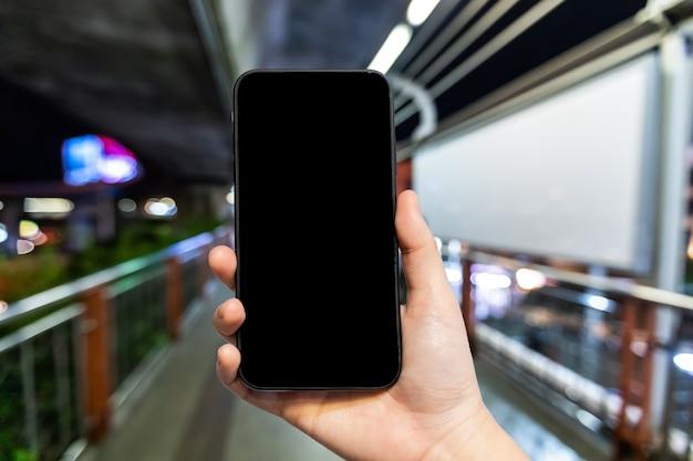 Uso femenino mano smartphone con pantalla negra vacía en el skywalk en bangkok