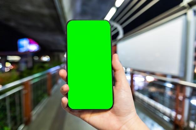 Uso femenino mano smartphone con pantalla verde vacía en el skywalk en bangkok