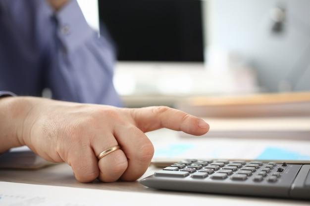 Uso del hombre calculadora analizando la inversión de la empresa