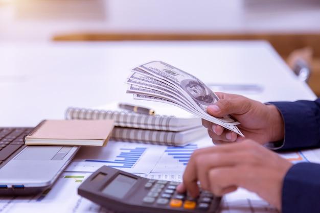 Uso de la mano contando el dinero del dólar en la inversión del escritorio de oficina y la propiedad para el concepto.