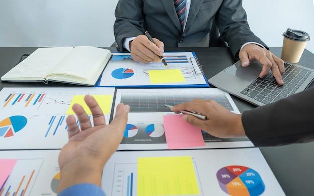 Uso de la mano portátil, reunión de equipo de mujeres empresarias y hombres de negocios para planificar estrategias para aumentar los ingresos comerciales
