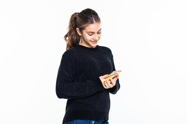 Uso de la mujer joven del teléfono celular aislado en la pared blanca