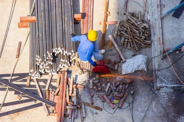 El uso del trabajador de la cortadora de acero industrial eléctrico trabaja en la construcción del área.