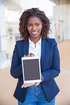 Usuario alegre feliz presentando copia espacio en la pantalla de la tableta