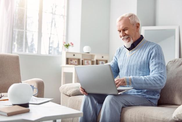 Usuario feliz. alegre anciano sentado en el sofá de la sala de estar y usando su computadora portátil, escribiendo un mensaje a sus amigos