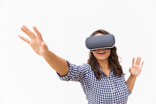 Usuario femenino positivo en gafas de realidad virtual tocando el aire y sonriendo