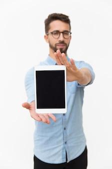 Usuario masculino de la tableta que muestra la pantalla en blanco