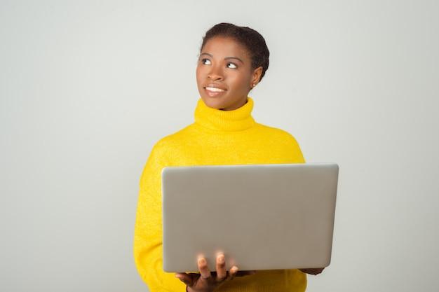 Usuario de pc positivo sonriente sosteniendo portátil y mirando a otro lado