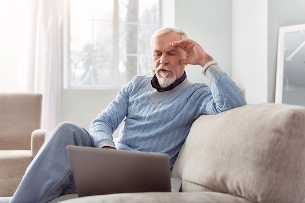 Usuario seguro. encantador anciano sentado en el sofá de la sala de estar y navegar por internet mientras descansa su mejilla en su mano