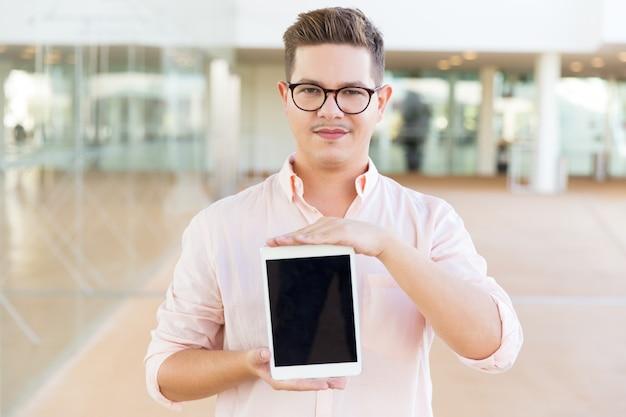Usuario de tableta seguro serio que presenta una pantalla en blanco