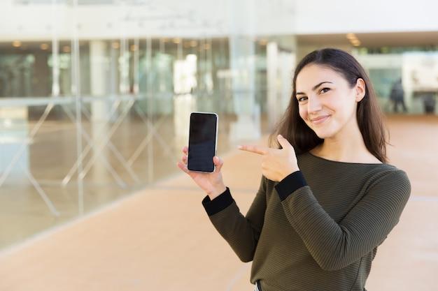 Usuario de teléfono celular satisfecho feliz apuntando a la pantalla en blanco