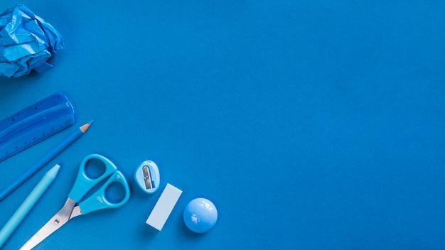 Utensilios azules de oficina en escritorio