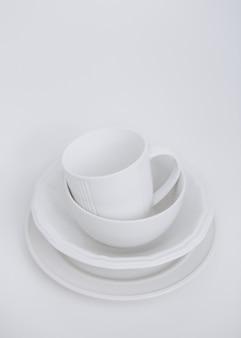 Utensilios blancos tres platos y una taza sobre un fondo blanco