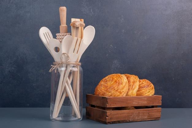 Utensilios de cocina con canasta de madera de gogals sobre mesa de mármol.