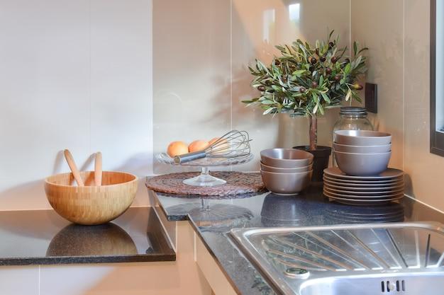 Utensilios de cocina de cerámica en la encimera de mármol y estantería.