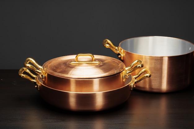 Utensilios de cocina de cobre vintage brillante sobre oscuro