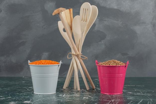 Utensilios de cocina con dos coloridos baldes de nueces en la pared de mármol.