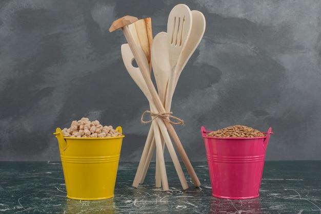 Utensilios de cocina con dos coloridos baldes de nueces sobre mesa de mármol.