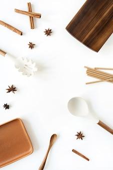 Utensilios de cocina con especias sobre superficie blanca