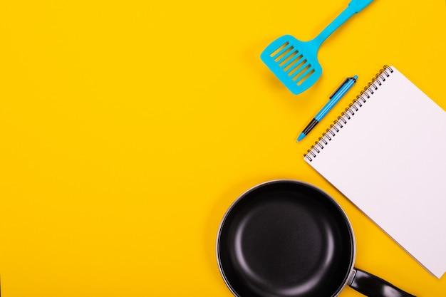 Utensilios de cocina y hoja limpia de papel aislado en amarillo