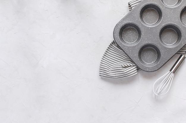 Utensilios de cocina para hornear - molde de metal para magdalenas batir en una servilleta de rayas arrugadas.