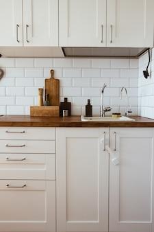 Utensilios de cocina de latón accesorios de chef cocina colgante con azulejos blancos de pared y tablero de madera ...