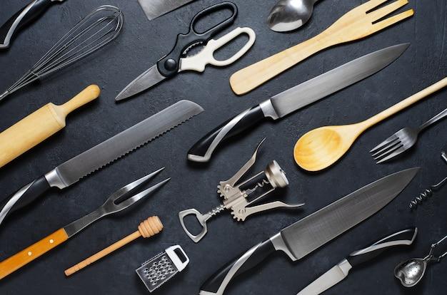 Utensilios de cocina de madera y metal. herramientas para cocinar. fondo oscuro lay flat