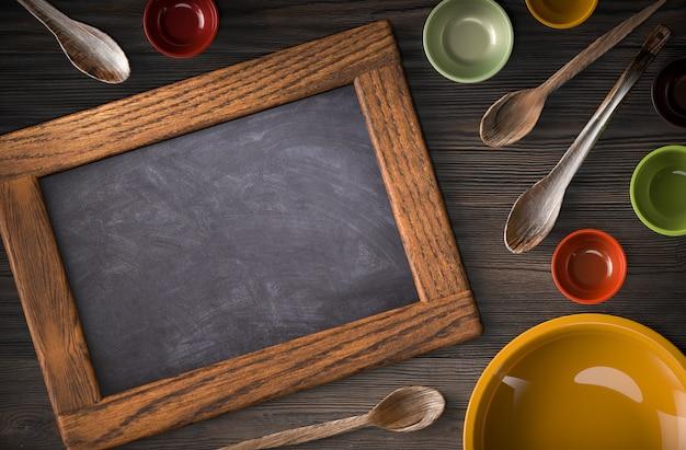 Utensilios de cocina de madera rústica y pizarra en blanco