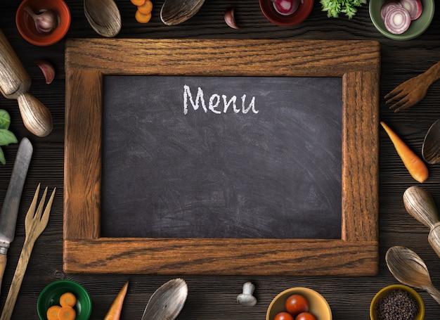 Utensilios de cocina de madera rústica, vegetales y alimentos variados y pizarra en blanco.