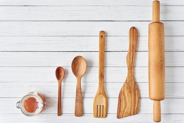 Utensilios de cocina de madera sobre fondo blanco de madera con espacio de copia