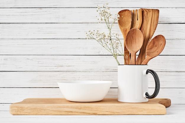Utensilios de cocina y tabla para cortar en mesa blanca.