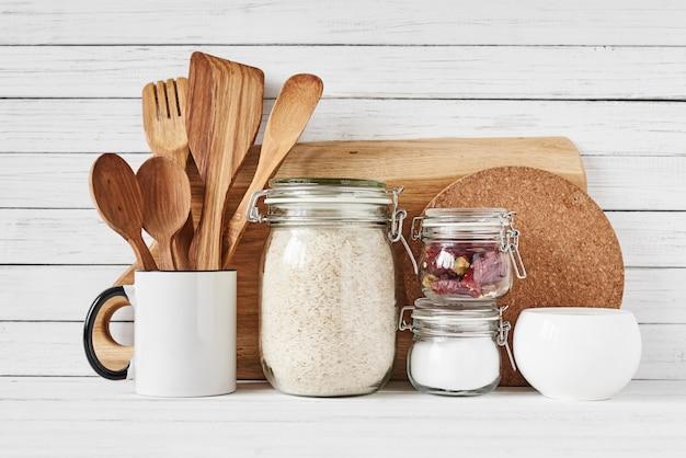 Utensilios de cocina y tabla de cortar en mesa blanca.