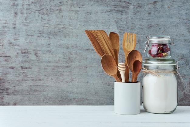 Utensilios de cocina en taza de cerámica sobre un fondo gris, espacio de copia