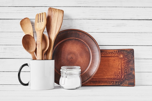 Utensilios de cocina en taza y plato marrón sobre blanco.
