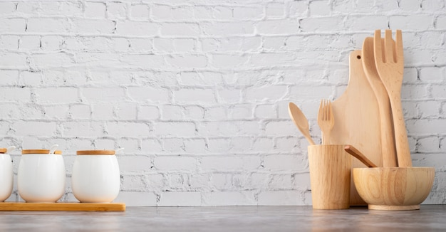 Utensilios de cocina y tazas de madera sobre fondo de textura de pared de ladrillo blanco.