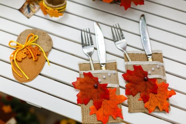 Utensilios de cocina, tenedores y cuchillos que sirven una mesa de madera decorada con hojas de otoño.