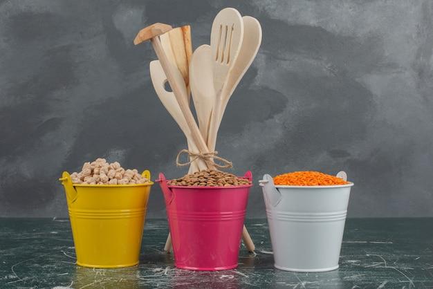 Utensilios de cocina con tres coloridos baldes de nueces en la pared de mármol.